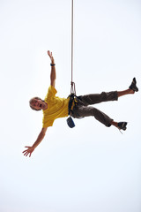 Happy rock climber hanging on rope