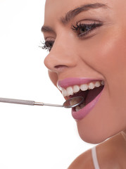 Smiling woman holding a dental mirror in her mouth