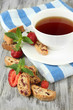 Cup of tea with cookies and strawberries on table close-up