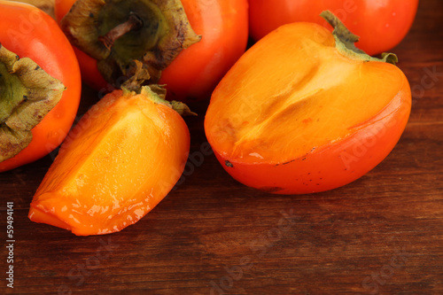 Ripe persimmons on wooden background
