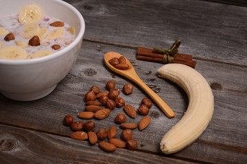 bowl of muesli and millk with fresh banana close up on wooden