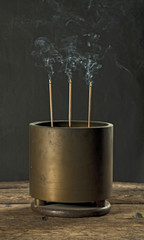 Antique incense burner on wooden table in dark background (Still