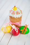 Easter eggs and cake decorated with a hen, wooden background