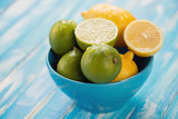 Glass bowl with lemons and limes, blue wooden background
