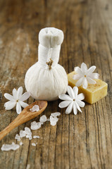 white blossoms with soap ,massage ball ,spoon on old wood
