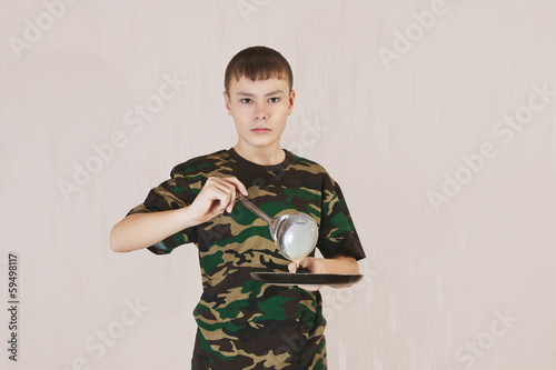 the boy pours dough for a frying pan