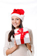 Beautiful young girl in santa hat with gifts box in hand