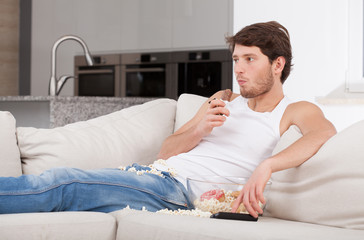 Bored man lying on couch