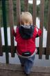 Junge steht an Zaun