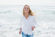 Smiling casual woman running at beach