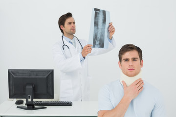 Patient in surgical collar while doctor examining spine x-ray be
