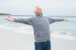 Senior man with arms outstretched at beach