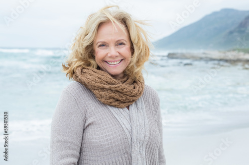 Smiling casual senior woman relaxing at beach