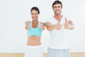 Happy fit couple gesturing thumbs up in fitness studio