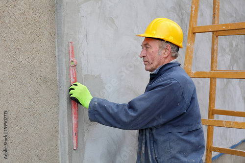 Worker control styrofoam insulation of wall with level tool