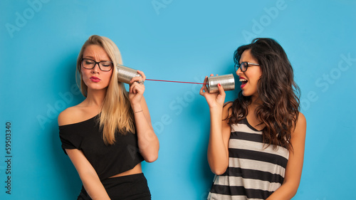 Blonde and brunette women talking with tin can telephone against - 59503340