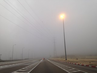 single car on an empty road in fog