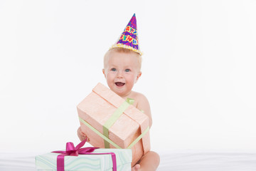 Happy beautiful baby in party hat holding present box.