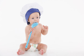 Cute little baby in toque with ladle
