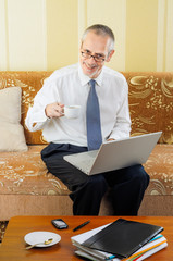 Senior Businessman with Computer Drinking Coffee
