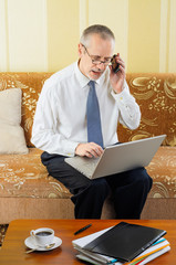 Senior Businessman with  Computer and Cellular Phone