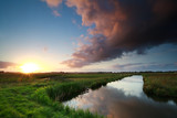 sunset over river on Dutch farmland