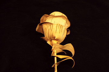 Rose flower made of birch bark on black velvet