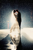 Bride and groom kissing under rain in the night