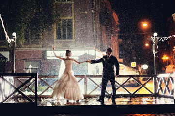 Bride and groom dancing in the night under rain