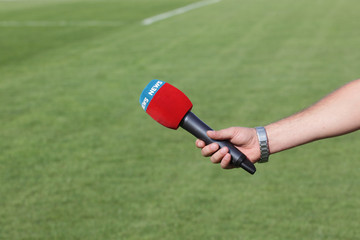 hand holding microphone for interview during a football mach