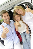 Cheerful family in car trunk showing thumbs up