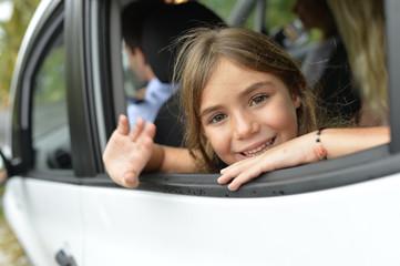 Little girl waving hand by car window