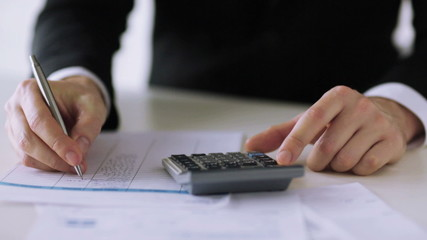 man with calculator filling a form
