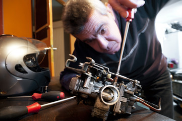 Mechanic repairs a carburetor