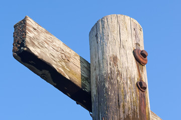 Old wooden post with cross member beam