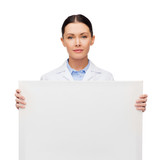 calm female doctor with white blank board