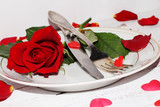 Romantic table setting  with roses plates and cutlery
