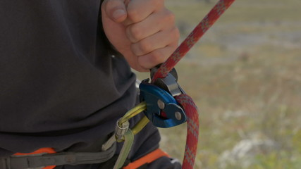 rock climbing rope passes through belay device