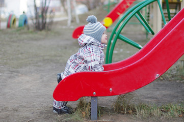 baby standing by slide on playground