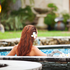 Beautiful woman relaxing in jacuzzi at spa center