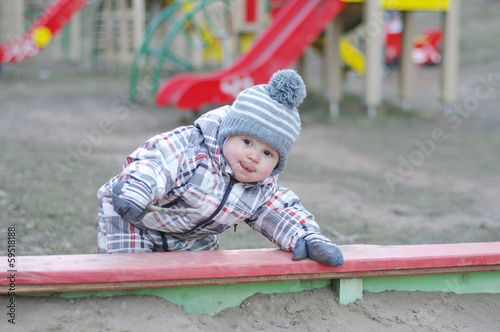 baby playing with sand on playground