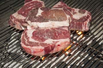 Ribeye steaks on a barbecue