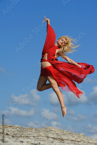 Beautiful blonde girl dancing with clouds