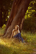 Romantic young woman sitting under a tree