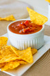 Spicy red salsa with a plate of tortilla chips, focus on the sal