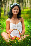 Beautiful girl sitting on grass floor and holding basket of appl