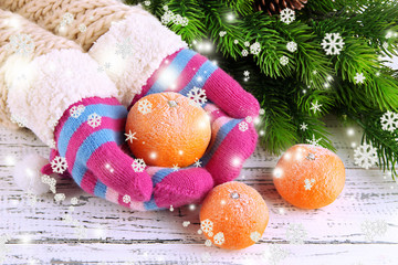 Hands in mittens holding tangerine on wooden background