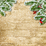 Christmas tree branch with snowfall on the wooden board