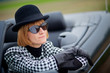 40s woman with sunglasses in a cabriolet