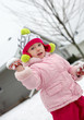 Happy little girl throwing snowball at winter